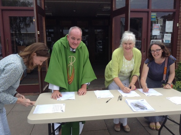 Fr Liam and parishioners signing the petition.